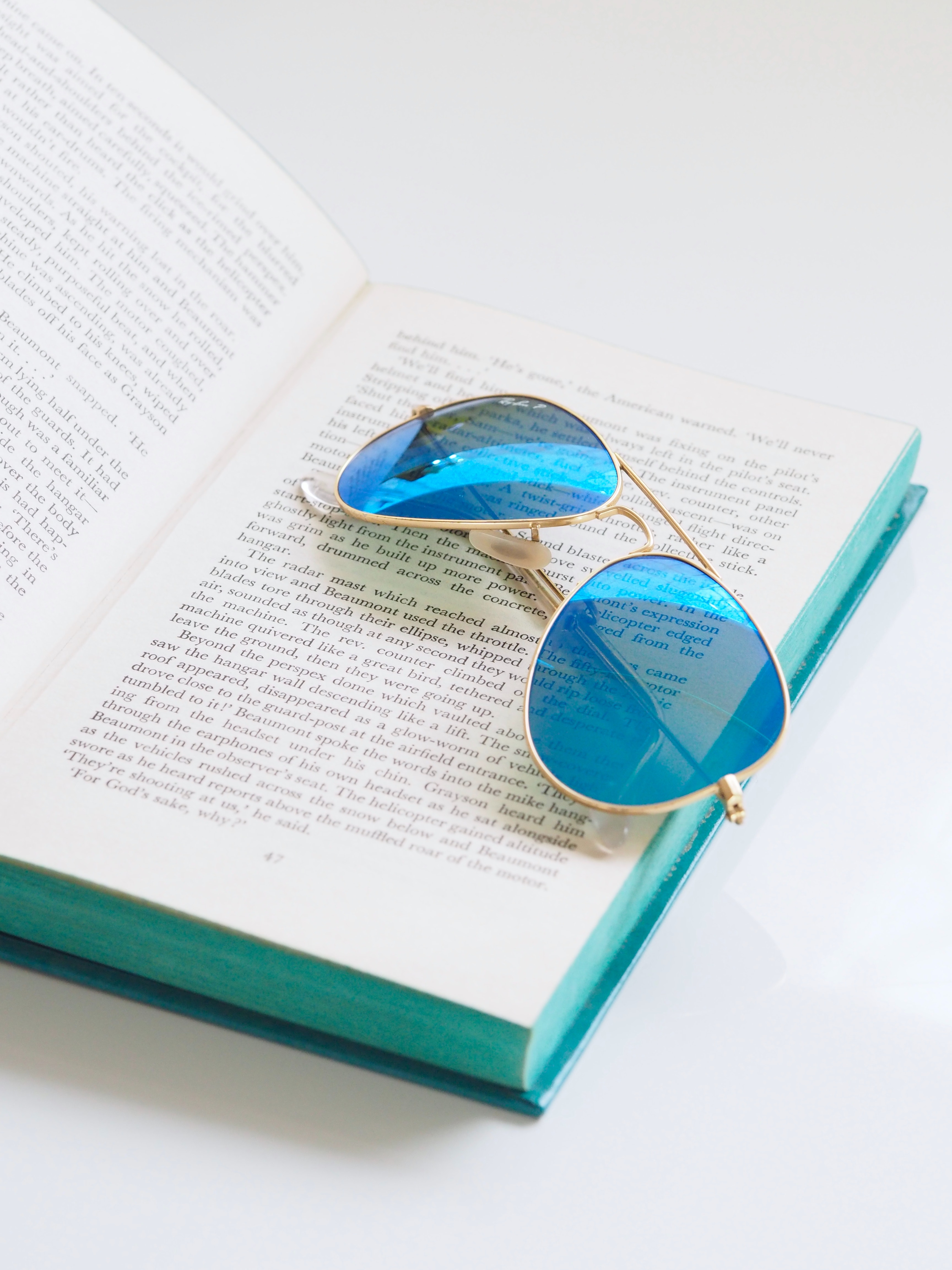 Content reading and feedback. Blue sunglasses on open book. Stock photo: https://stocksnap.io